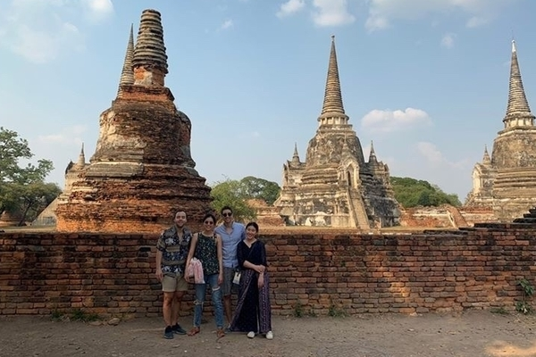 Four students stand in front of a large temple in Thailand